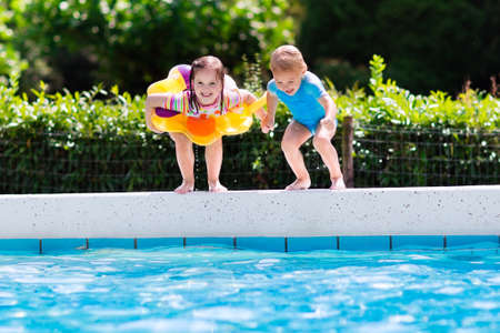 Photo for Happy little girl and boy holding hands jumping into outdoor swimming pool in a tropical resort during family summer vacation. Kids learning to swim. Water fun for children. - Royalty Free Image