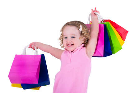 Photo pour Little girl  in a pink dress holding colorful shopping bags. Child in a shop buying clothes. Sale in a store. Kids with purchases. - image libre de droit