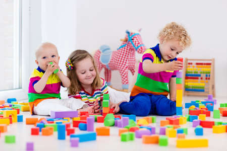 Photo pour Happy preschool age children play with colorful plastic toy blocks. Creative kindergarten kids build a block tower. Educational toys for toddler or baby. Siblings having fun playing together. - image libre de droit