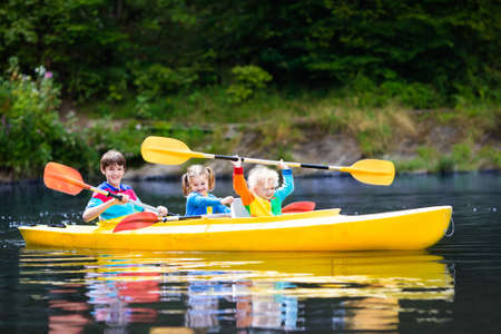 Foto de Happy family with three kids enjoying kayak ride on beautiful river. Little girl, toddler boy and teenager kayaking on hot summer day. Water sport and camping fun. Canoe and boat for children. - Imagen libre de derechos