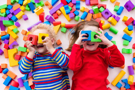 Foto de Happy preschool age children play with colorful plastic toy blocks. Creative kindergarten kids build a block tower. Educational toys for toddler or baby. Top view from above. - Imagen libre de derechos