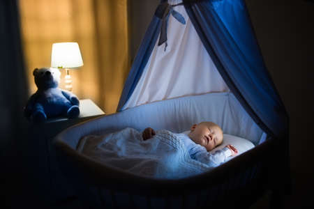 Foto de Adorable baby sleeping in blue bassinet with canopy at night. Little boy in pajamas taking a nap in dark room with crib, lamp and toy bear. Bed time for kids. Bedroom and nursery interior. - Imagen libre de derechos