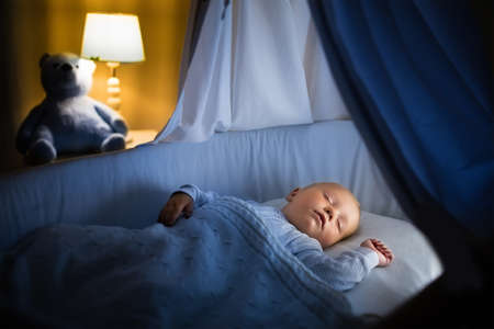Photo pour Adorable baby sleeping in blue bassinet with canopy at night. Little boy in pajamas taking a nap in dark room with crib, lamp and toy bear. Bed time for kids. Bedroom and nursery interior. - image libre de droit
