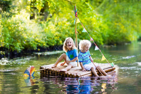 Photo for Two children on wooden raft catching fish with a colorful net in a river and playing with water on hot summer day. Outdoor fun and adventure for kids. Boy and girl in toy boat. Sailor role game. - Royalty Free Image