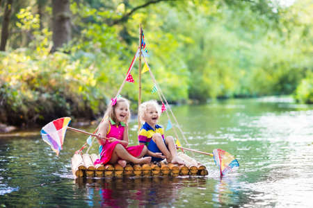 Photo pour Two children on wooden raft catching fish with a colorful net in a river and playing with water on hot summer day. Outdoor fun and adventure for kids. Boy and girl in toy boat. Sailor role game. - image libre de droit