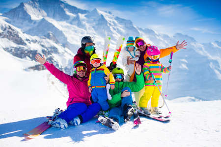 Foto de Family ski vacation. Group of skiers in Swiss Alps mountains. Adults and young children, teenager and baby skiing in winter. Parents teach kids alpine downhill skiing. Ski gear and wear, safe helmets. - Imagen libre de derechos