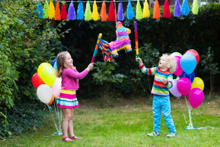 Photo for Kids birthday party. Group of children hitting pinata and playing with balloons. Family and friends celebrating birthday outdoors in decorated garden. Outdoor celebration with active games. - Royalty Free Image