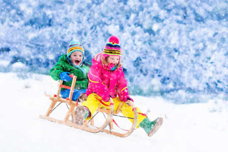 Photo pour Little girl and boy enjoy a sleigh ride. Child sledding. Toddler kid riding a sledge. Children play outdoors in snow. Kids sled in Alps mountains in winter. Outdoor fun for family Christmas vacation. - image libre de droit