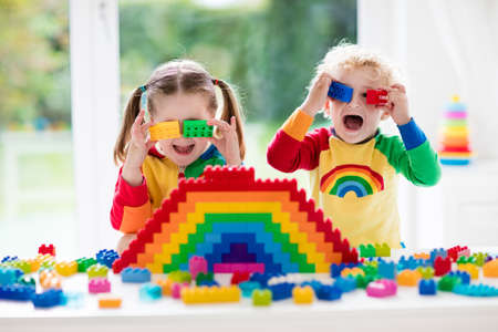 Photo for Child playing with colorful toys. Little girl and funny curly baby boy with educational toy blocks. Children play at day care or preschool. Mess in kids room. Toddlers build a tower in kindergarten. Focus on girl. - Royalty Free Image