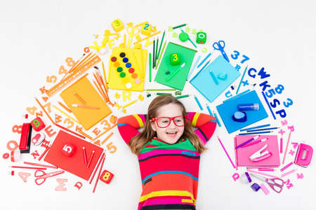 Photo pour Little girl with school supplies, books, drawing and painting tools and materials. Happy back to school student. Art and crafts for kids. Child learning rainbow colors, alphabet letters and numbers. - image libre de droit