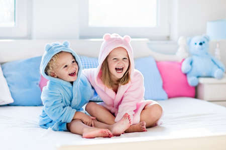Photo pour Happy laughing kids, boy and girl in soft bathrobe after bath play on white bed with blue and pink pillows in sunny bedroom. Child in clean and dry towel. Wash, infant hygiene, health and skin care. - image libre de droit
