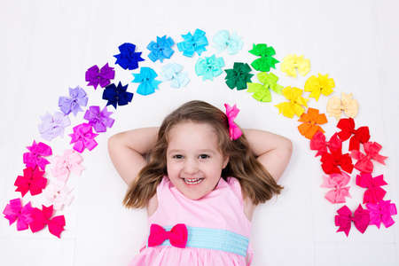 Photo pour Little girl in pink pastel dress choosing colorful hair accessories. Bow and ribbon for kids. Hair style and accessory for children. Choice of bows. Rainbow ribbons for girls. View from above on white - image libre de droit