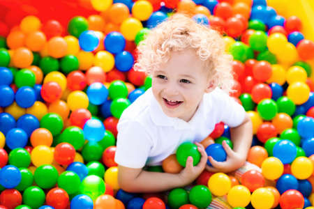 Photo pour Happy laughing boy having fun in ball pit on birthday party in kids amusement park and indoor play center. Child playing with colorful balls in playground ball pool. Activity toys for little kid. - image libre de droit