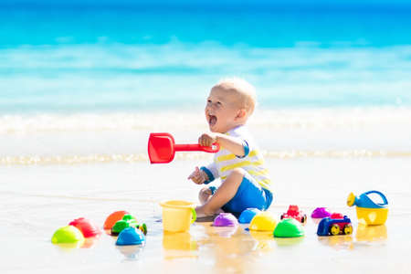 Foto de Cute laughing baby boy wearing sun protection rash guard playing with bucket and shovel on tropical beach during family summer sea vacation. Swimwear and beach toys for kids. Child digging in sand. - Imagen libre de derechos