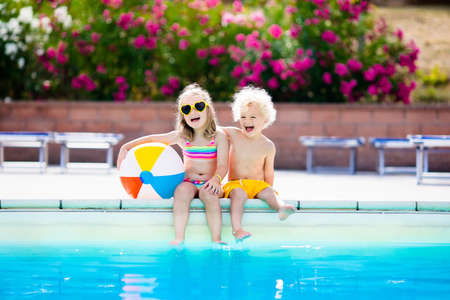 Photo pour Kids playing at outdoor swimming pool. Little girl and boy play and swim in resort pool on tropical beach island summer family vacation. Swim and eye wear, sun protection, water toys for children. - image libre de droit