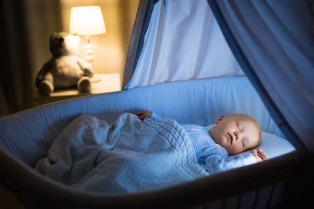Photo pour Adorable baby drinking milk in blue bassinet with canopy at night. Little boy in pajamas with formula bottle getting ready to sleep in dark room with crib, lamp and toy bear. Bed time drink for kids. - image libre de droit