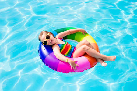 Photo pour Happy little girl playing with colorful inflatable ring in outdoor swimming pool on hot summer day. Kids learn to swim. Child water toys. Children play in tropical resort. Family beach vacation. - image libre de droit