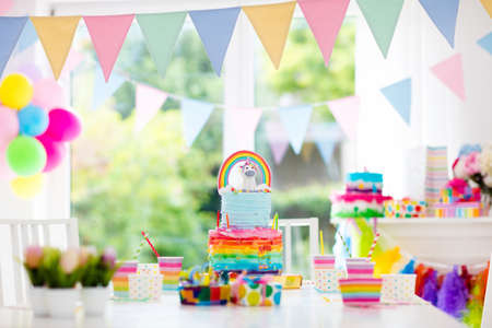 Foto de Kids birthday party decoration and cake. Decorated table for child birthday celebration. Rainbow unicorn cake for little girl. Room with festive balloons, colorful banners in baby pastel color. - Imagen libre de derechos