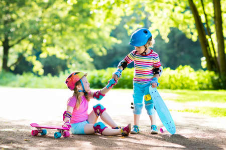 Foto de Children riding skateboard in summer park. Little girl and boy learn to ride skate board, help and support each other. Active outdoor sport for kids. Child skateboarding. Preschooler kid skating. - Imagen libre de derechos