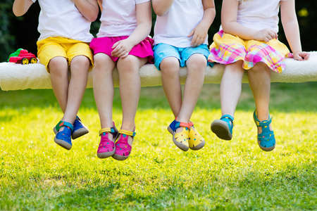 Photo pour Footwear for children. Group of preschool kids wearing colorful leather shoes. Sandal summer shoe for young child and baby. Preschooler playing outdoor. Child clothing, foot wear and fashion. - image libre de droit