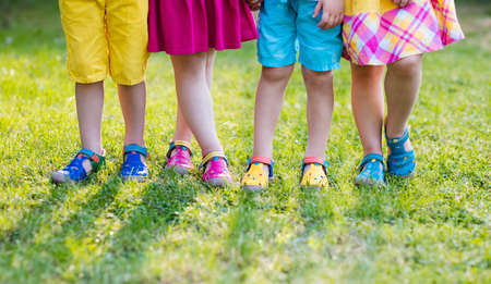 Foto de Footwear for children. Group of preschool kids wearing colorful leather shoes. Sandal summer shoe for young child and baby. Preschooler playing outdoor. Child clothing, foot wear and fashion. - Imagen libre de derechos
