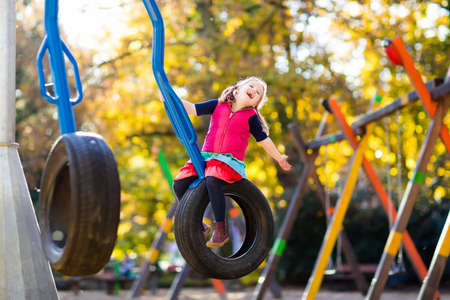 Photo pour Kids on playground Children play in autumn park. Child on slide and swing on sunny fall day. Preschool or kindergarten yard. Daycare for young kid. Girl on play ground. Outdoor fun in autumn. - image libre de droit