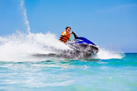 Foto de Teen age boy skiing on water scooter. Young man on personal watercraft in tropical sea. Active summer vacation for school child. Sport and ocean activity on beach holiday. - Imagen libre de derechos