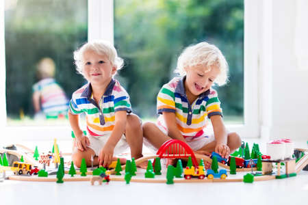 Foto de Kids play with toy train railway. Children playing with wooden trains. Toys for little boy. Two brothers build rail road and blocks at home or daycare, preschool. Kindergarten educational games. - Imagen libre de derechos