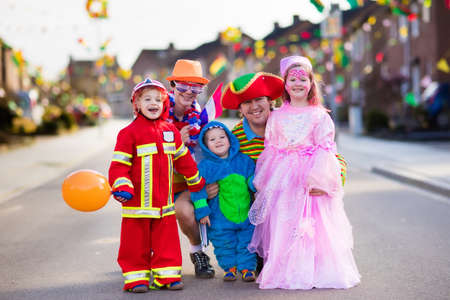 Foto de Kids and parents on Halloween trick or treat. Family in Halloween costumes with candy bags walking in decorated street trick or treating. Baby and preschooler celebrating carnival. Child costume. - Imagen libre de derechos