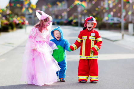 Photo pour Kids on Halloween trick or treat. Children in Halloween costumes with candy bags walking in decorated city neighborhood trick or treating. Baby and preschooler celebrating carnival wearing costume. - image libre de droit