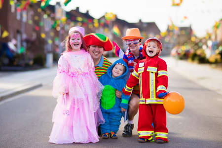 Photo pour Kids and parents on Halloween trick or treat. Family in Halloween costumes with candy bags walking in decorated street trick or treating. Baby and preschooler celebrating carnival. Child costume. - image libre de droit