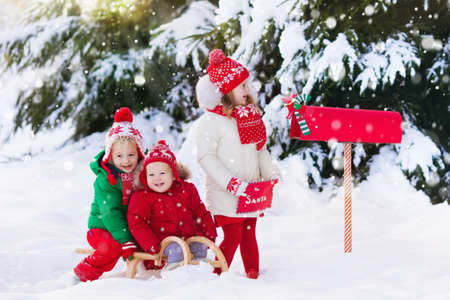 Foto de Happy children in knitted reindeer hat and scarf holding letter to Santa with Christmas presents wish list at red mail box in snow under Xmas tree in winter forest. Kids sending post to North Pole. - Imagen libre de derechos