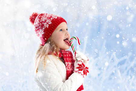 Foto de Child eating candy apple on winter fair. Kids eat toffee apples on Christmas market in snow. Outdoor fun on snowy day. Family vacation in Xmas season. Children play outdoors. Winter fashion for kids. - Imagen libre de derechos