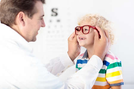 Photo pour Child at eye sight test. Little kid selecting glasses at optician store. Eyesight measurement for school kids. Eye wear for children. Doctor performing eye check. Boy with spectacles at letter chart. - image libre de droit