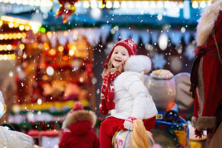 Photo for Happy little girl in warm jacket and red knitted Nordic hat and scarf riding carousel horse during family trip to traditional German Christmas market. Kids at Xmas outdoor fair on snowy winter day. - Royalty Free Image