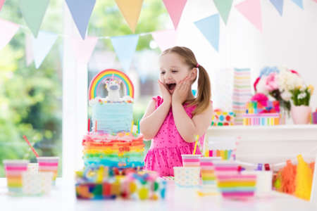 Foto de Kids birthday party with colorful pastel decoration and unicorn rainbow cake. Little girl with sweets, candy and fruit. Balloons and banner at festive decorated table for child or baby birthday party. - Imagen libre de derechos