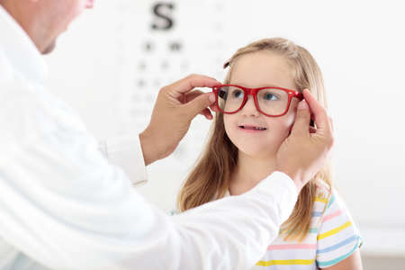 Photo pour Child at eye sight test. Little kid selecting glasses at optician store. Eyesight measurement for school kids. Eye wear for children. Doctor performing eye check. Girl with spectacles at letter chart. - image libre de droit