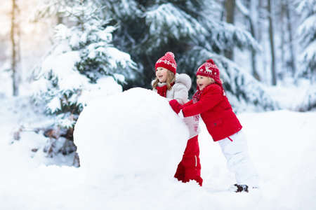 Photo pour Children build snowman. Kids building snow man playing outdoors on sunny snowy winter day. Outdoor family fun on Christmas vacation. Boy and girl play snow balls. Winter clothing for baby and toddler. - image libre de droit