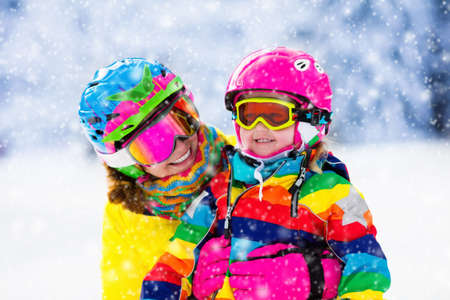 Foto de Family ski vacation. Group of skiers in Swiss Alps mountains. Mother and child skiing in winter. Parents teach kids alpine downhill skiing. Ski gear and wear, safe helmets. - Imagen libre de derechos