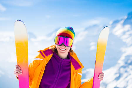 Foto de Young active woman skiing in mountains. Female skier kid with safety helmet, goggles and poles enjoying sunny winter day in Swiss Alps. Ski race for adults. Winter and snow sport in alpine resort. - Imagen libre de derechos