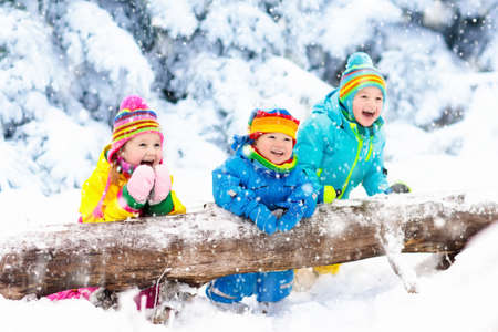 Photo pour Kids playing in snow. Children play outdoors on snowy winter day. Boy and girl catching snowflakes in snowfall storm. Brother and sister throwing snow balls. Family Christmas vacation activity. - image libre de droit