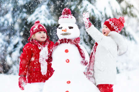 Photo for Children build snowman. Kids building snow man playing outdoors on sunny snowy winter day. Outdoor family fun on Christmas vacation. Boy and girl play snow balls. Winter clothing for baby and toddler. - Royalty Free Image