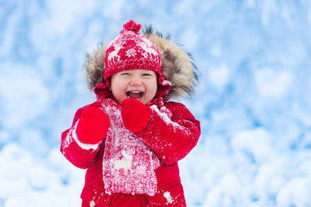 Foto de Baby playing with snow in winter. Little toddler boy in red jacket and Xmas reindeer knitted hat catching snowflakes in winter park on Christmas. Kids play in snowy forest. Children catch snow flakes - Imagen libre de derechos