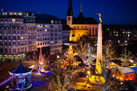 Foto de Christmas fair in Luxemburg. Aerial view of traditional Xmas market in old European city center. City decorated for winter holidays. Amusement and shopping for Christmas presents in Europe. - Imagen libre de derechos