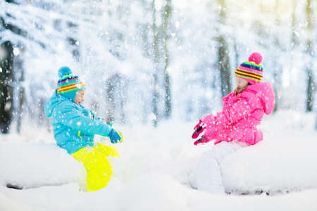 Foto de Kids playing in snow. Children play outdoors on snowy winter day. Boy and girl catching snowflakes in snowfall storm. Brother and sister throwing snow balls. Family Christmas vacation activity. - Imagen libre de derechos