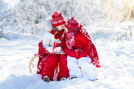 Photo pour Kids sledding in winter forest. Children drink hot chocolate on sled under warm blanket. Boy and girl play in snow on Christmas vacation. Xmas family fun. Kid with cocoa on sledge. Child with sleigh. - image libre de droit