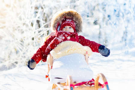 Photo for Sled and snow fun for kids. Baby sledding in snowy winter park. Little boy in warm red jacket and knitted hat sitting in sheepskin footmuff. Kid on sleigh. Child on sledge. Family Christmas vacation. - Royalty Free Image