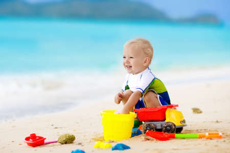 Photo pour Child playing on tropical beach. Little girl digging sand at sea shore. Family summer vacation. Kids play with water and sand toys. Ocean and island fun. Travel with young children. Asia holiday. - image libre de droit