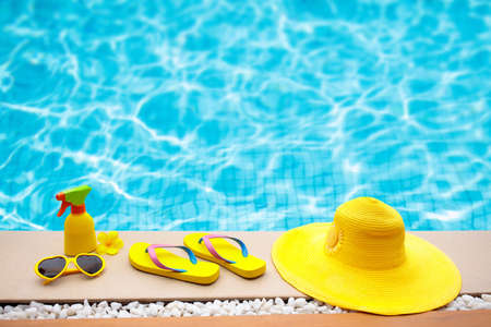 Foto de Swimming pool accessories flat lay. Top view of beach items on pool deck. Flip flops, bikini and hat, sun glasses. Water toys. Summer vacation in tropical resort. Copy space. Colorful beach wear. - Imagen libre de derechos