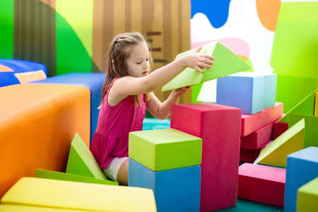 Photo pour Child playing with colorful construction toy blocks. Educational toys for young kids. Kindergarten or preschool play room. Toddler kid at day care playground. Girl building house with block at daycare - image libre de droit